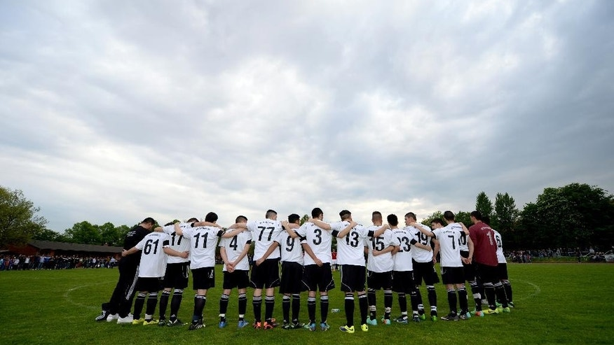 """In this picture taken Wednesday, April 30, 2014, the soccer team of 17-year old German exchange student Diren Dede SC Teutonia 1910 holds a minute of silence prior to a soccer match in Hamburg, northern Germany. The father of the student who was killed in the United States criticized the country's gun laws upon his arrival in Montana where his son was fatally shot. Celal Dede told the German news agency dpa Thursday that """"America cannot continue to play the cowboy."""" (AP Photo/dpa, Daniel Reinhardt)"""