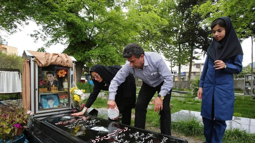 In this pictures taken on Monday, April 28, 2014, Iranian woman Samereh Alinejad, left, and her husband Abdolghani Hosseinzadeh wash the grave stone of their sons Amir Hossein and Abdollah while their daughter Fatemeh looks on in a cemetery in the city of Royan about 146 miles (235 kilometers) north of the capital Tehran, Iran. Amir Hossein was killed in a motorcycle crash and Abdollah was killed in a street brawl. Alinejad tells The Associated Press that she had felt she could never live with herself if the man who killed her son Abdollah were spared from execution. But in the last moment, she pardoned him in an act that has made her a hero in her hometown, where banners in the streets praise her family's mercy. (AP Photo/Vahid Salemi)
