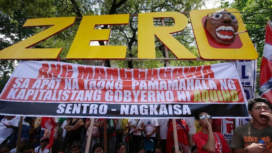 Workers shout slogans as they hold a rally near the Presidential Palace to mark the Labor Day celebrations on Thursday, May 1, 2014 in Manila, Philippines. Various labor groups nationwide held protests, mostly to demand wage hikes, better working conditions and an end to corruption in the government. The sign reads: Workers Have Zero Benefits In The Four Years of Capitalist Government of Aquino. (AP Photo/Bullit Marquez)