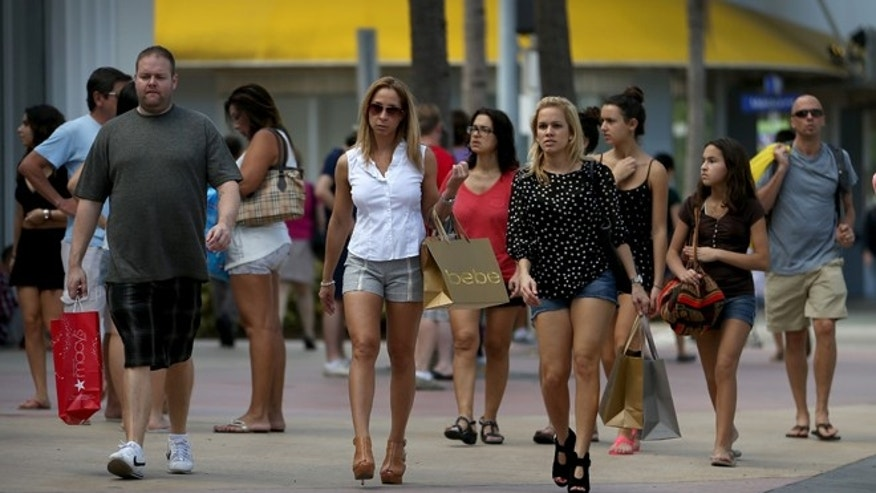 MIAMI BEACH, FL - DECEMBER 24:  People walk with their shopping bags along Lincoln Road Mall on the day before Christmas on December 24, 2013 in Miami, Beach Florida.  Retail stores are hoping last minute shoppers give their holiday sales a boost. (Photo by Joe Raedle/Getty Images)