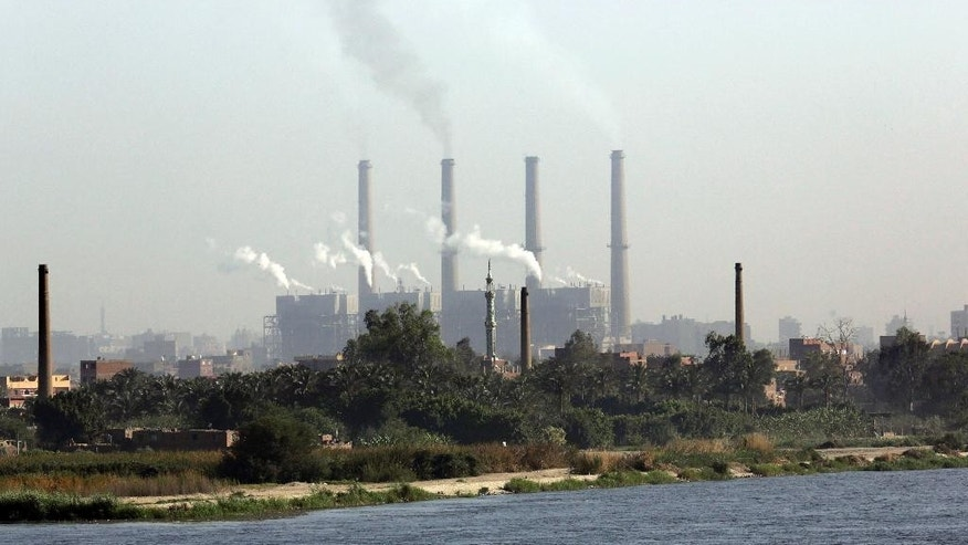 In this Monday, April 28, 2014 photo, smoke billows from the Shoubra El-Kheima power station, which is owned by the North Cairo electricity distribution company, on the Nile river in Cairo, Egypt. Rolling blackouts have already been hitting neighborhoods of Cairo daily throughout the winter, when electricity usage is lower. Now summer's heat is coming, and Egypt's crippling energy crisis is threatening to mount, creating an immediate political liability for the new president to be elected next month, expected to be former army chief Abdel-Fattah el-Sissi.(AP Photo/Amr Nabil)