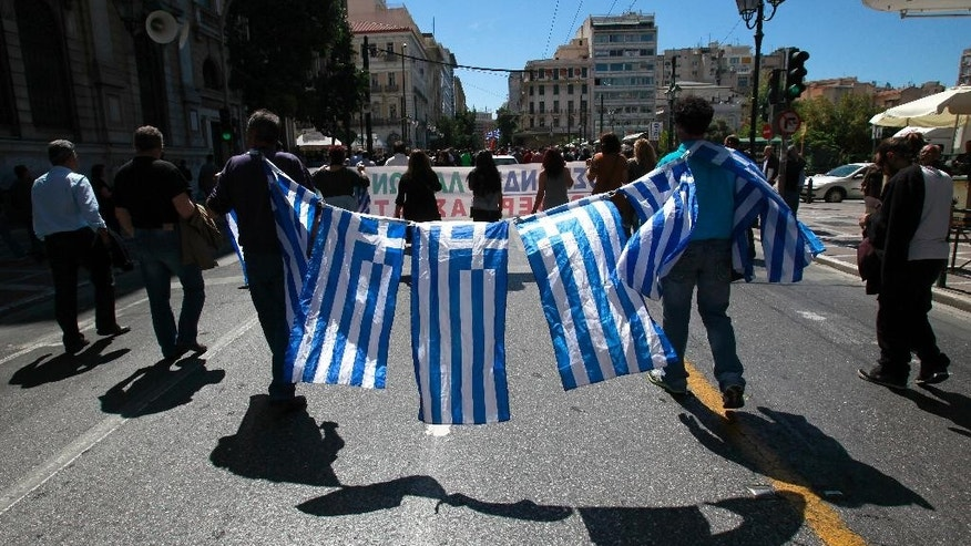 Greek farmers market vendors hold national flags during a protest in Athens, Friday May 2, 2014, after their trading association launched an indefinite strike Monday. The market vendors are the latest professional group in Greece to protest a sweeping liberalization drive demanded by rescue creditors. (AP Photo/Dimitri Messinis)