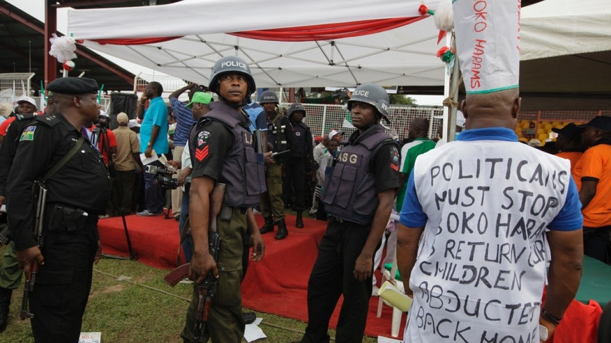 Police stand guard at a demonstration in Lagos calling on Nigeria's government to rescue kidnapped school girls. (Reuters)