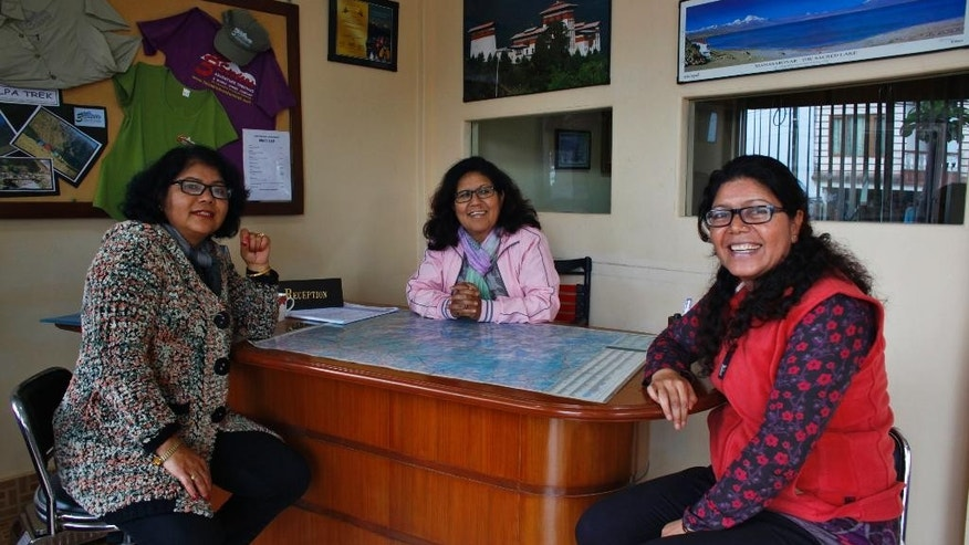 In this March 1, 2014 photo, from left,  Dicky, Lucky, and Nicky Chettri pose for photographs at the 3 Sisters Adventure Trekking Company office in Pokhara, Nepal. When Lucky, Dicky and Nicky Chettri tried to break into Nepal's male-dominated trekking industry 20 years ago, competitors tried to run them out of business. Men threatened them, harassed them - even filed bogus police reports against them. (AP Photo/Niranjan Shrestha)