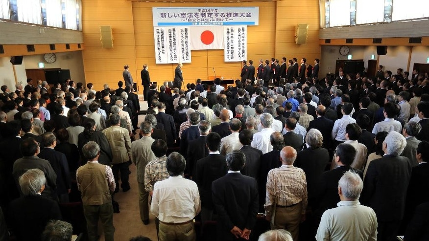 In this Thursday, May 1, 2014, guests and audience stand as they listen to the Japanese national anthem at a meeting of a pro-constitution amendment group in Tokyo. Japan is marking the 67th anniversary of its postwar constitution on May 3, 2014 with growing debate over whether to revise the war-renouncing document. Prime Minister Shinzo Abe's ruling conservative party has long advocated revision but been unable to sway public opinion. Now he proposes that the government reinterpret the constitution so it can loosen the reins on its military without having to win approval for constitutional change. (AP Photo/Eugene Hoshiko)
