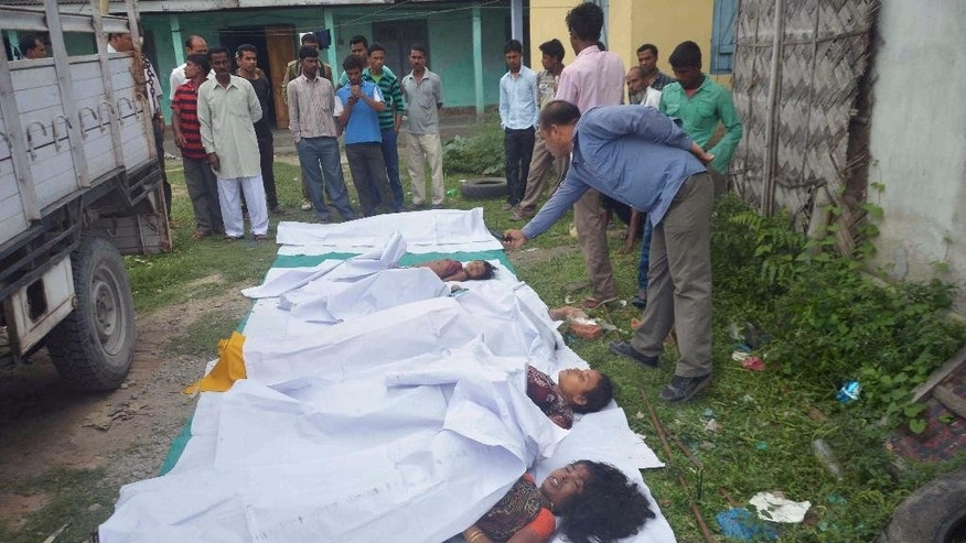 Bodies of victims are laid in a row on the ground in Kokrajhar, in the northeastern Indian state of Assam, Friday, May 2, 2014. Separatist militants opened fire with automatic weapons on Muslim villagers in remote northeastern India, killing at least 10 people, including two children, in two attacks, police said Friday. Four people were wounded. (AP Photo)