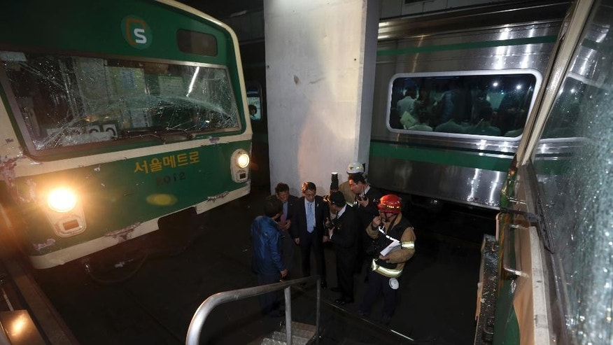 Investigators inspect the site where two subway trains collided at Sangwangshipri subway station in Seoul, South Korea, Friday, May. 2, 2014. A subway train ran into another train at the station Friday, causing minor injuries for scores of people, a city official said. (AP Photo/Yonhap, Park Dong-ju)  KOREA OUT