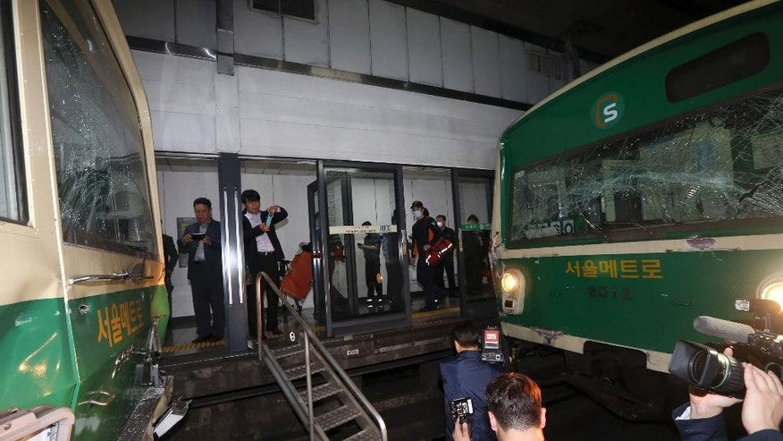 Windows of two subway trains remain broken after their collision at Sangwangshipri subway station in Seoul, South Korea, Friday, May. 2, 2014. A subway train ran into another train at the station Friday, causing minor injuries for scores of people, a city official said. (AP Photo/Yonhap, Park Dong-ju)  KOREA OUT