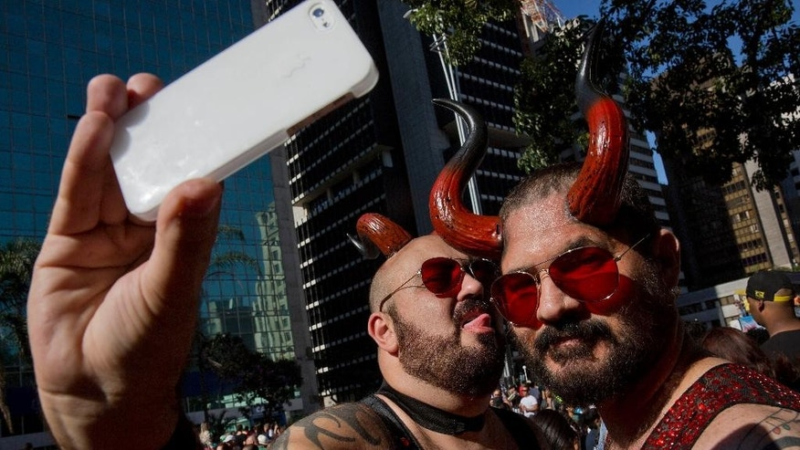 Revelers take a selfie during the annual Gay Pride Parade in Sao Paulo, Brazil, Sunday, May 4, 2014. Gay rights advocates are calling for a Brazilian law against discrimination as they gather by the hundreds of thousands in Sao Paulo for one of the world's largest gay pride parades. (AP Photo/Andre Penner)
