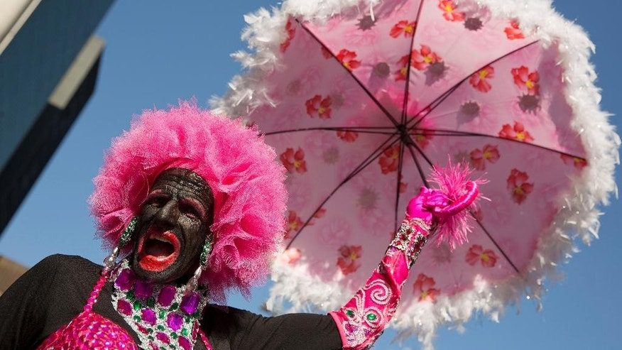 A reveler poses for photos during the annual Gay Pride Parade in Sao Paulo, Brazil, Sunday, May 4, 2014.  Gay rights advocates are calling for a Brazilian law against discrimination as they gather by the hundreds of thousands in Sao Paulo for one of the world's largest gay pride parades. (AP Photo/Andre Penner)