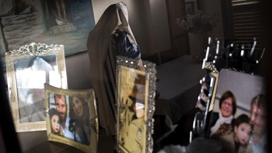 In this photo taken Wednesday, April 30, 2014, Jewish ultra-Orthodox military captain Moshe Prigan, is reflected in a mirror in his library as he prepares for his morning prayer at home in the ultra-Orthodox Jewish town of Bnei Brak, near Tel Aviv, Israel. Prigan doesn't just serve in the military, he also recruits other ultra-Orthodox Jewish men to enlist, something the cloistered community has traditionally avoided doing. The issue of military service is at the core of a cultural war over the place of ultra-Orthodox Jews in Israeli society today. (AP Photo/Oded Balilty)