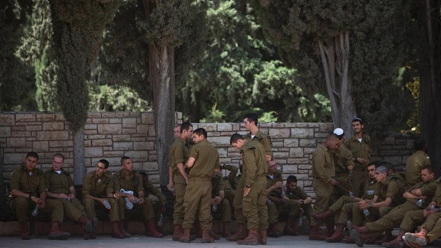 Israeli soldiers rest during preparations for Memorial Day ceremonies at Kiryat Shaul Military cemetery in Tel Aviv, Israel, Sunday, May 4, 2014. Israel will mark the annual Memorial Day in remembrance of soldiers who died in the nation's conflicts, beginning at dusk Sunday until Monday evening. (AP Photo/Oded Balilty)