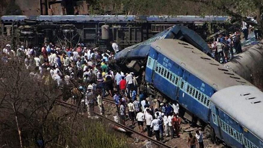 May 4, 2014: People gather around a passenger train that derailed near Roha station, 70 miles south of Mumbai, Maharashtra state, India. The cause of the accident was not immediately known.