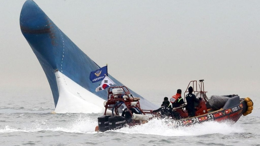 FILE - In this April 16, 2014 file photo, South Korean coast guard officers try to rescue passengers from the Sewol ferry as it sinks in the water off the southern coast near Jindo, south of Seoul, South Korea. The doomed ferry Sewol exceeded its cargo limit on 246 trips - nearly every voyage it made in which it reported cargo - in the 13 months before it sank, according to documents that reveal the regulatory failures that allowed passengers by the hundreds to set off on an unsafe vessel. And it may have been more overloaded than ever on its final journey. (AP Photo/Yonhap, File) KOREA OUT