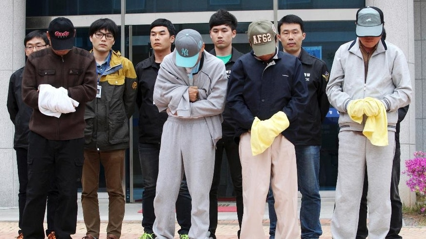 Crew members of the sunken ferry Sewol prepare to leave a court which issued their arrest warrant, in Mokpo, South Korea, Saturday, April 26, 2014. All 15 surviving crew members involved in the ferry's navigation have been arrested, accused of negligence and failing to protect passengers. Prosecutors also detained three employees of the ferry owner who handled cargo, and have raided the offices of the ship owner, the shipping association and the register. Heads of the shipping association and the register offered to resign in the wake of the disaster. (AP Photo/Yonhap)  KOREA OUT