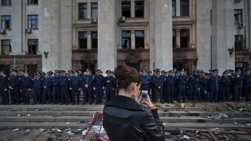 May 3, 2014: A woman takes a photo as police troops guard the burnt trade union building in Odessa, Ukraine. Tensions in Ukraine heightened sharply after at least 42 people died in clashes between government supporters and opponents in Odessa on Friday. (AP Photo/Vadim Ghirda)