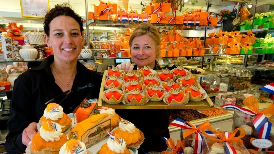 FILE - In this April 23, 2013 file photo Sandra Terpstra, left, and Linda Clewits pose with trays of cakes made for Queen's Day at a Arnold Cornelis pastry shop in Amsterdam, Netherlands. The restaurant chain Dunkin' Donuts is testing whether that deep-fried classic American snack, the doughnut, can compete successfully against entrenched competition from some of the world's most famous sweet snacks in their own homelands, including the waffle in Belgium, apple strudel in Austria and the Danish in Denmark. (AP Photo/Peter Dejong, File)