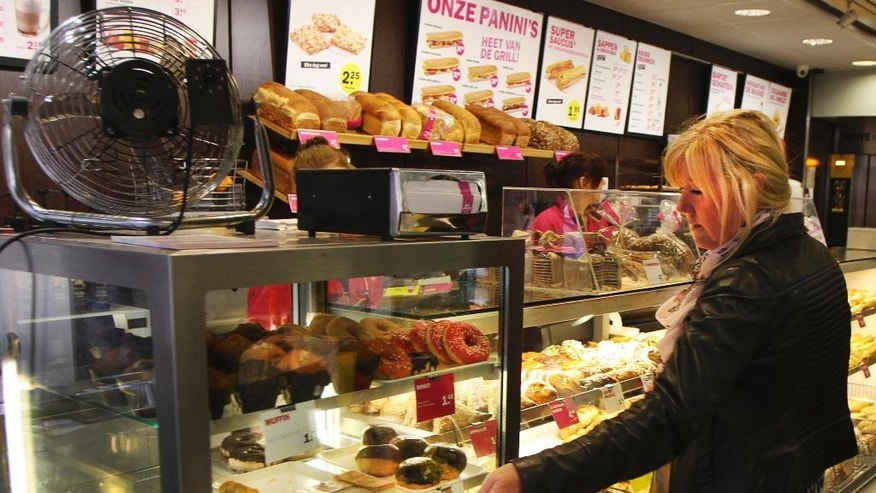 In this photo taken Friday, May 2, 2014, a woman shops for a pastry at a Bakker Bart store in Amsterdam, Netherlands. Treats on display include typical Dutch pastry such as: Bossche bollen, appeltaart, tompouces, soesjes, Luikse wafels, and puddingbroodjes. They also sell a doughnut. The restaurant chain Dunkin' Donuts is testing whether that deep-fried classic American snack, the doughnut, can compete successfully against entrenched competition from some of the world's most famous sweet snacks in their own homelands, including the waffle in Belgium, apple strudel in Austria and the Danish in Denmark. (AP Photo/Margriet Faber)