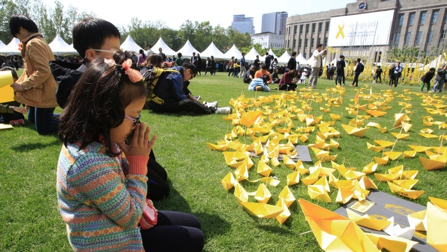 May 5, 2014 - A girl prays in front of paper ships bearing messages for the victims of the sunken ferry Sewol at a group memorial altar in Seoul, South Korea. More than 300 people are dead or missing in the water off the southern coast in the disaster that caused widespread grief, anger and shame.