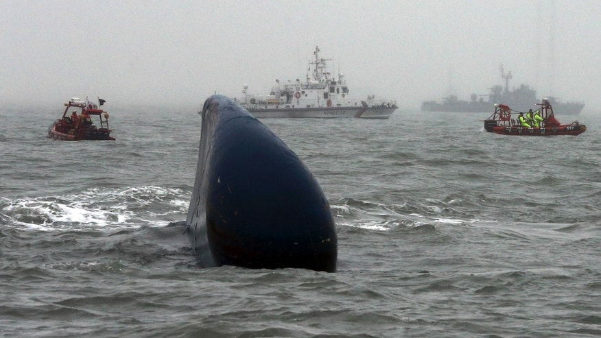 April 18, 2014 - FILE photo of South Korean Coast Guard officers searching missing passengers aboard the ferry Sewol, center, in the water off the southern coast near Jindo, South Korea.