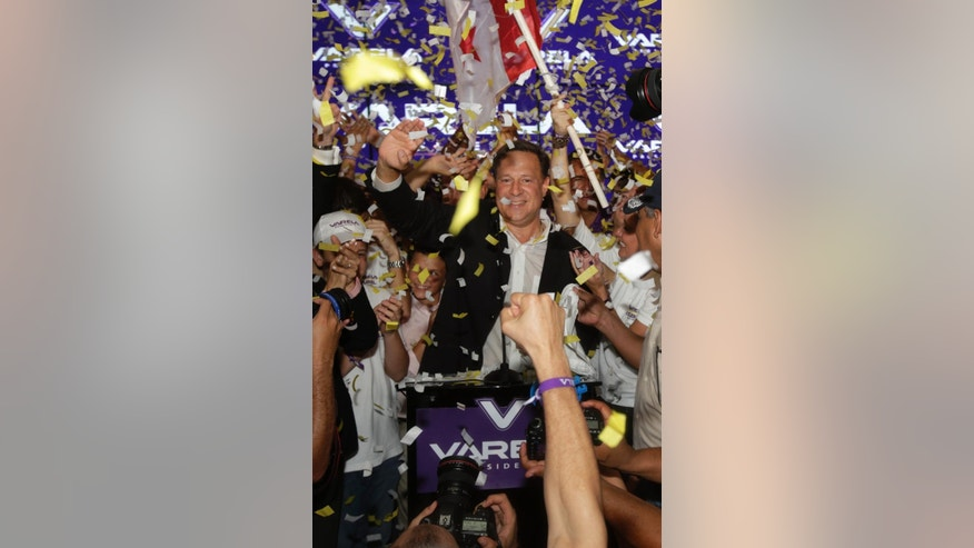 Juan Carlos Varela, Panama's president elect, waves to supporters after delivering his acceptance speech in Panama City, Sunday, May 4, 2014. Varela was declared the victor of Panama's presidential election, thwarting an attempt by former ally President Ricardo Martinelli to extend his grip on power by electing a hand-picked successor. (AP Photo/Arnulfo Franco)