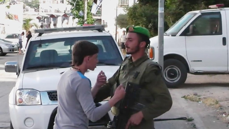 In this image taken from video obtained from Youth Against Settlements, a group of Palestinian activists, which has been authenticated based on its contents and other AP reporting, a Palestinian teen confronts an Israeli soldier in the West Bank city of Hebron. The reprimand of an Israeli soldier, caught on video cursing and pointing a cocked gun toward the head of a Palestinian teen, has triggered the biggest outpouring of frustration by Israeli soldiers in years about their service in the West Bank. (AP Photo/Youth Against Settlements)