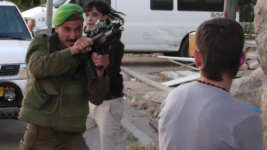 In this image taken from video obtained from Youth Against Settlements, a group of Palestinian activists, which has been authenticated based on its contents and other AP reporting, an Israeli soldier points his gun at a Palestinian teen in the West Bank city of Hebron. The reprimand of an Israeli soldier _ caught on video cursing and pointing a cocked gun toward the head of a Palestinian teen _ has triggered the biggest outpouring of frustration by Israeli soldiers in years about their service in the West Bank. (AP Photo/Youth Against Settlements)