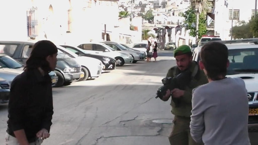 In this image taken from video obtained from Youth Against Settlements, a group of Palestinian activists, which has been authenticated based on its contents and other AP reporting, an Israeli soldier points his gun at a Palestinian teen in the West Bank city of Hebron. The reprimand of an Israeli soldier, caught on video cursing and pointing a cocked gun toward the head of a Palestinian teen, has triggered the biggest outpouring of frustration by Israeli soldiers in years about their service in the West Bank. (AP Photo/Youth Against Settlements)