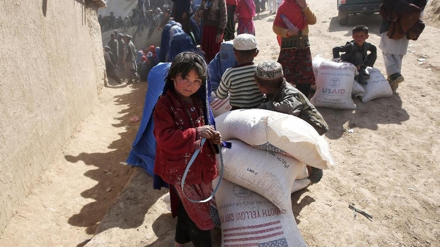An Afghan girl stands near of food donations near the site of Friday's landslide that buried Abi-Barik village in Badakhshan province, northeastern Afghanistan, Tuesday, May 6, 2014. Authorities tried to help families displaced by the torrent of mud that swept through Abi-Barik village after hundreds were killed. (AP Photo/Massoud Hossaini)