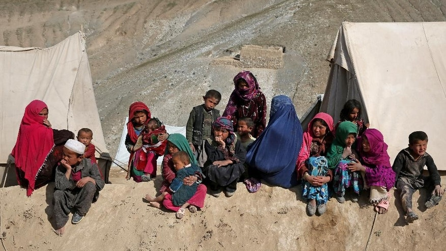 Survivors sit in front of their tents near the site of Friday's landslide that buried Abi-Barik village in Badakhshan province, northeastern Afghanistan, Tuesday, May 6, 2014. Authorities tried to help families displaced by the torrent of mud that swept through Abi-Barik village after hundreds were killed. (AP Photo/Massoud Hossaini)