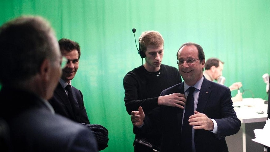 France's President Francois Hollande, right, smiles after an interview with BFM television journalist in Paris, Tuesday, May 6, 2014. Hollande celebrates Tuesday his second anniversary in charge. (AP Photo/Thibault Camus, Pool)