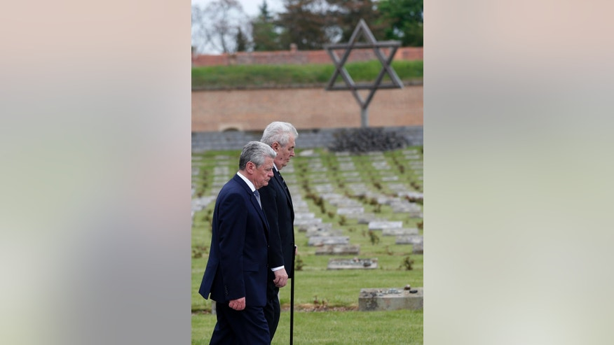 Czech Republic's President Miloz Zeman, right, and his Germany's counterpart Joachim Gauck, left, walk to lay a wreath of flowers at a memorial in former nazi concentration camp of Terezin in Terezin, Czech Republic, Tuesday, May 6, 2014. Gauck is to Czech Republic on a three-day official visit. (AP Photo/Petr David Josek)