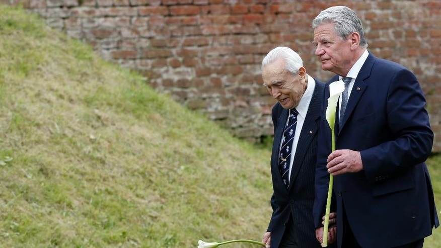 Germany's President Joachim Gauck, right, walks with holocaust survivor Felix Kolmer, left, to lay a flower as they meet at  the former nazi concentration camp of Terezin in Terezin, Czech Republic, Tuesday, May 6, 2014. Gauck is to Czech Republic on a three-day official visit. (AP Photo/Petr David Josek)