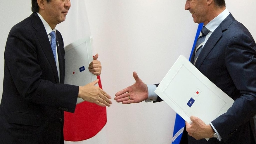 Japan's Prime Minister Shinzo Abe, left, and NATO Secretary General Anders Fogh Rasmussen shake hands after signing a cooperation agreement at NATO headquarters in Brussels on Tuesday, May 6, 2014. Abe will, in a two-day visit, meet with NATO, EU and Belgian officials. (AP Photo/Virginia Mayo, Pool)