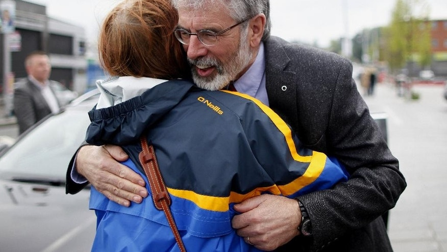 Sinn Fein President Gerry Adams gets a warm welcome from a woman on the Andersonstown road in West Belfast, Northern Ireland, Monday, May 5, 2014.  A police evidence file documenting Gerry Adams' Irish Republican Army career has been delivered to British state prosecutors in Belfast, but experts say the chances of the Sinn Fein leader being charged are slim on legal, political and particularly national-security grounds. Adams, 65, walked free Sunday after five days of police interrogation and declared his innocence in the unsolved 1972 abduction, slaying and secret burial of a Belfast mother of 10, Jean McConville. (AP Photo/Peter Morrison)