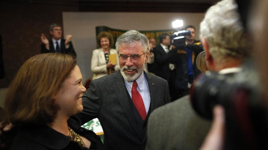Sinn Fein president Gerry Adams, center, is welcomed from a colleague during a party rally in West Belfast, Northern Ireland, Monday May 5, 2014. Adams walked free Sunday after five days of police interrogation and declared his innocence in the unsolved 1972 abduction, slaying and secret burial of a Belfast mother of 10, Jean McConville. (AP Photo/Peter Morrison)