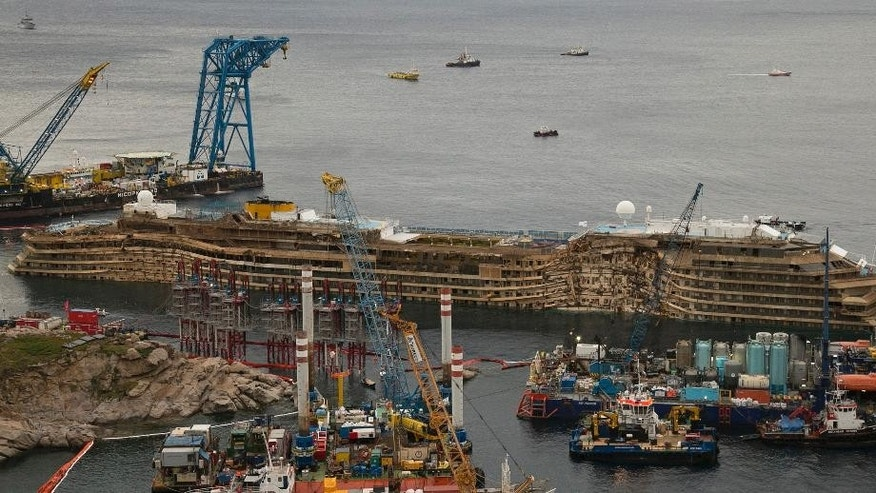 FILE -- In  this Sept. 17, 2013 file photo, The Costa Concordia is seen after it was lifted upright on the Tuscan Island of Giglio, Italy. One of the tanks fastened to the shipwrecked Costa Concordia cruise liner to help prepare it for removal to land has shifted, Tuesday, may 6, 2014. The consortium overseeing the operation said in a statement that the cause was under investigation and that there was no damage to the ship. Workers fastened the first tank to the starboard side of the ship last week. The tanks, 19 in all, were being filled with water to help stabilize the Concordia, now resting on an artificial seabed after it was set upright in September. (AP Photo/Andrew Medichini)