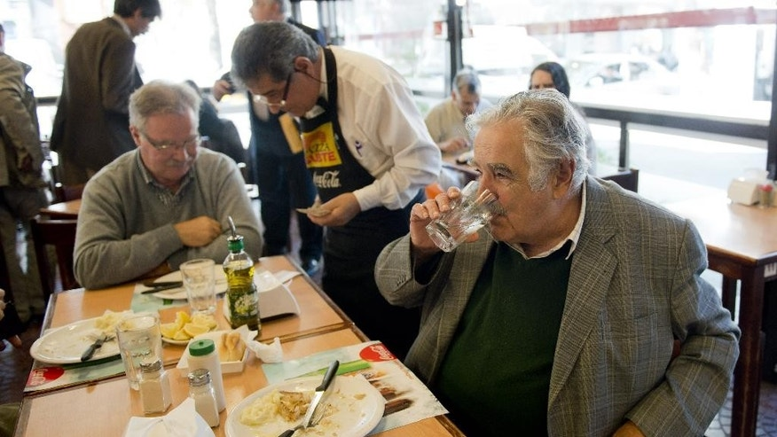 Uruguay's President Jose Mujica finishes lunch at El Subte pizzeria where he stopped to eat with friends in downtown Montevideo, Uruguay, Tuesday, May 6, 2014. Mujica is set to sign a law creating the country's legal marijuana market, making Uruguay the first country in the world to create a nationwide market regulating the cultivation, sale and use of legal marijuana. (AP Photo/Matilde Campodonico)