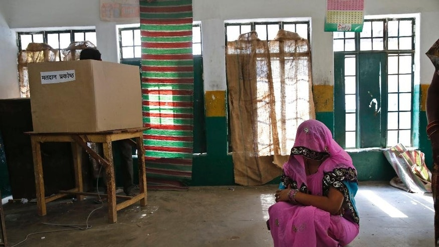 An Indian woman sits on the floor after casting her vote as she waits for her husband, left, to finish voting during the eighth phase of voting of the Indian parliamentary elections in Allahabad, Uttar Pradesh state, India, Wednesday, May 7, 2014. The multiphase voting across the country runs until May 12, with results for the 543-seat lower house of parliament expected on May 16. (AP Photo/ Rajesh Kumar Singh)