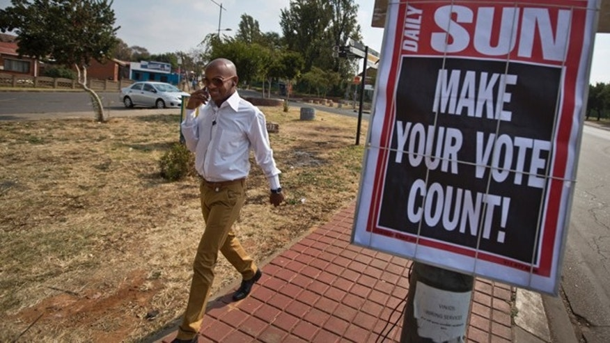 May 6, 2014: A man speaking on his mobile phone walks past a placard from Daily Sun newspaper urging people to vote, in the Soweto township of Johannesburg, South Africa. (AP Photo/Ben Curtis)