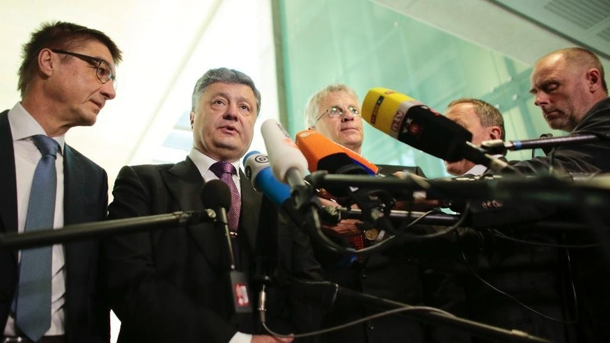 Ukrainian presidential candidate and businessman Petro Poroshenko, 2. from left, briefs the media after a meeting with Germany's Christian Union's deputy faction leader Andreas Schockenhoff, left, and other law makers in Berlin, Germany, Wednesday, May 7, 2014. The Ukrainian government is planing a presidential election on May 25, 2014, (AP Photo/Markus Schreiber)