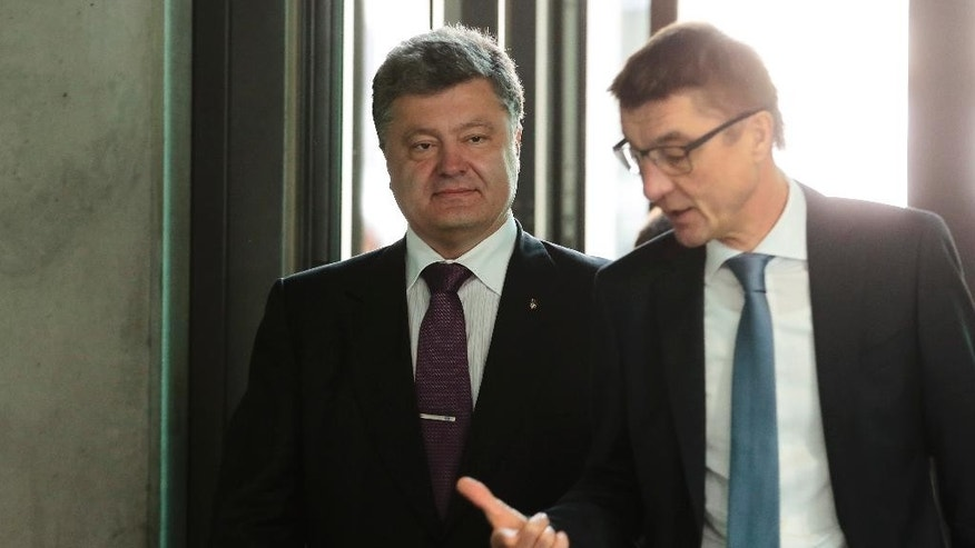 Ukrainian presidential candidate and businessman Petro Poroshenko, left, is accompanied by Germany's Christian Union's ruling party deputy faction leader Andreas Schockenhoff prior to a meeting in Berlin, Germany, Wednesday, May 7, 2014. The Ukrainian government is planing a presidential election on May 25, 2014. (AP Photo/Markus Schreiber)
