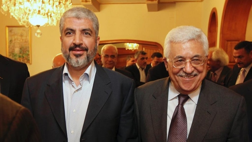 FILE - In this file photo provided on Nov. 24, 2011, by the office of Khaled Mashaal, Palestinian Hamas leader Khaled Mashaal, left, and Palestinian President Mahmoud Abbas are seen together during their meeting in Cairo, Egypt. A spokesman said Monday, May 5, 2014, that Mashaal and Abbas have held a rare meeting in Doha, Qatar, and agreed to move forward with a reconciliation deal between their rival movements. Abbas was in Doha for a grandson's college graduation. (AP Photo/Office of Khaled Meshaal, File)