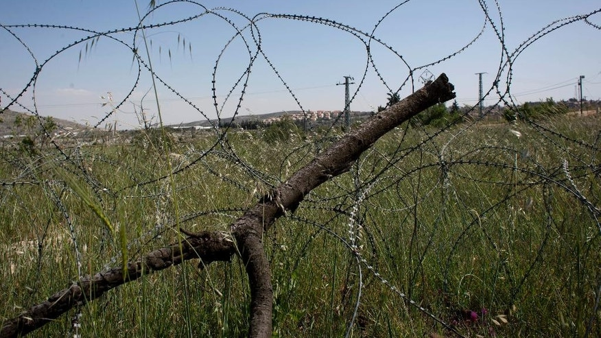 In this April 17, 2014 photo, barbed wire surrounds the Silwad village's land that is dedicated by the Israeli settlement of Ofra, seen in the background, for an illegal wastewater treatment plant, north of the West Bank city of Ramallah. (AP Photo/Nasser Nasser)