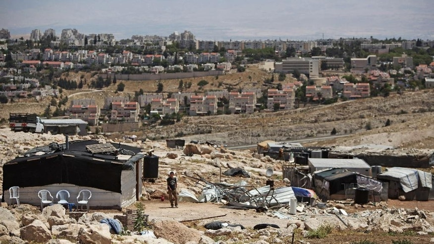 In this May 1, 2014 photo, a Palestinian bedouin stands in front of a demolished shelter in the Palestinian Bedouin community Jabal al-Baba, with the Israeli settlement of Maaleh Adumim in the background. Between 1997 and 2007, Israel evicted about 150 Jahalin families from their communities to make way for the expansion of the settlement of Maaleh Adumim, across a main highway from where E-1 would be built. (AP Photo/Majdi Mohammed)