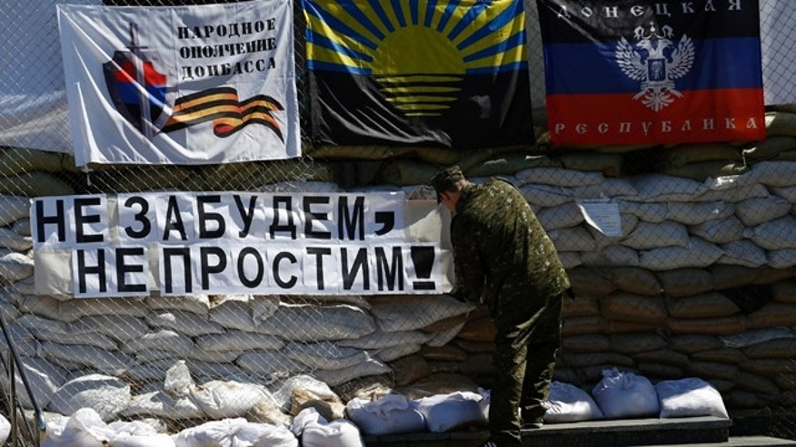 May 8, 2014: A pro-Russian gunman sets a banner which reads 'Do not forget, do not forgive!' in front of the city hall decorated with flags of the self-proclaimed Donetsk People's Republic, in the center of Slovyansk, eastern Ukraine (AP Photo/Darko Vojinovic)