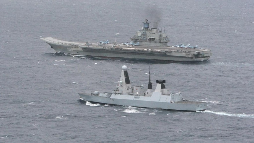 "An undated aerial photo made available by Britain's Ministry of Defence, Thursday, May 8, 2014 showing HMS Dragon, foreground, with the Russian aircraft carrier 'Admiral Kuznetsov' in the English Channel. The Royal Navy warship met and tracked a Russian task force group as it entered the English Channel in an operation that the Ministry of Defense repeatedly stressed was a routine matter. HMS Dragon, a Type 45 destroyer, monitored the movement of the seven-strong Russian group led by the aircraft carrier Admiral Kuznetsov. The navy says that once the ships spotted each other they ""sailed close by as a standard 'meet and greet.' '' (AP Photo/Ministry of Defence)"