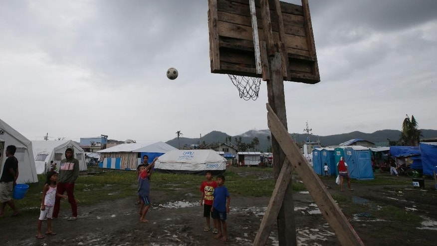 FILE - In this February 13, 2014 file photo, typhoon survivors play basketball at a tent city in Tacloban city, Leyte province in central Philippines. There are signs of progress since the monster storm slammed into the Philippines on Nov. 8, leaving more than 7,300 dead or missing and flattening hundreds of thousands of homes and other buildings. Many survivors have started rebuilding and debris is being slowly cleaned up and carted away. But enormous work remains. As of the end of April, more than 2 million people are living without adequate shelter, the United Nations Office for the Coordination of Humanitarian Affairs said. Access to water and sanitation also remains a challenge. (AP Photo/Bullit Marquez, File)