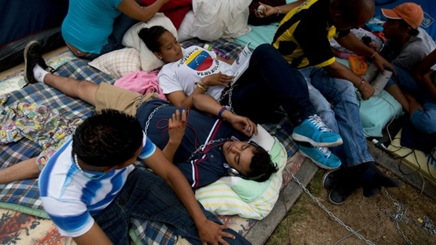April 29, 2014: Students lie on a sidewalk chained to a nearby tree in protest against Venezuela's President Nicolas Maduro outside the UN headquarters in Caracas.