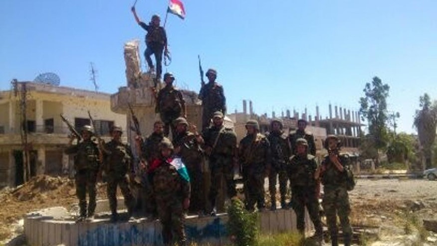 FILE - In this Wednesday, June 5, 2013 file photo released by the Syrian official news agency SANA, Syrian army troops hold up national flags in the town of Qusair, near the Lebanon border, Homs province, Syria. Two years ago, it seemed almost inevitable that President Bashar Assad would be toppled. Almost no one thinks that now. As he prepares for elections through which he is set to claim another seven-year mandate for himself, the momentum in the civil war is clearly in Assad's favor. (AP Photo/SANA, File)